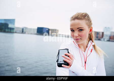 Female athlete training outdoors, using a smartphone to monitor her progress. Fit and sporty young athlete wearing - Stock Photo