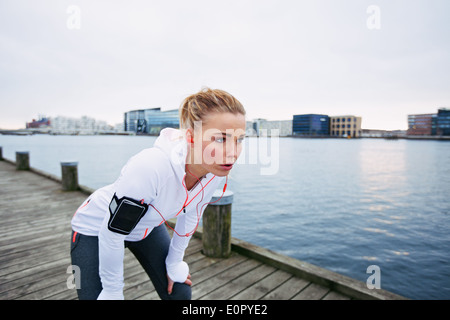 Female runner standing bent over and catching her breath after a running session along river. Young woman taking - Stock Photo