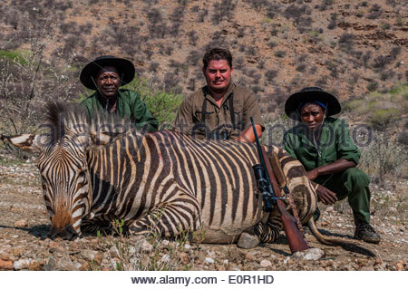A professional hunter and two helpers pose with a trophy animal (a zebra) that he shot on a hunting farm in Namibia. - Stock Photo