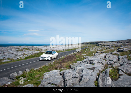 White Car on Sunny Day on Road and Touring Route through the Burren in County Clare along the Wild Atlantic Way - Stock Photo