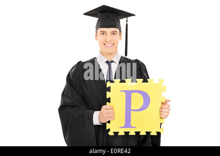 Male student holding a piece of puzzle with the letter p on it - Stock Photo