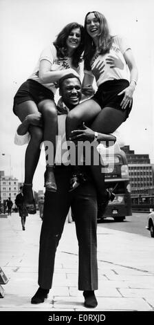 Boxer Smokin' Joe Frazier holding two women on his shoulders - Stock Photo