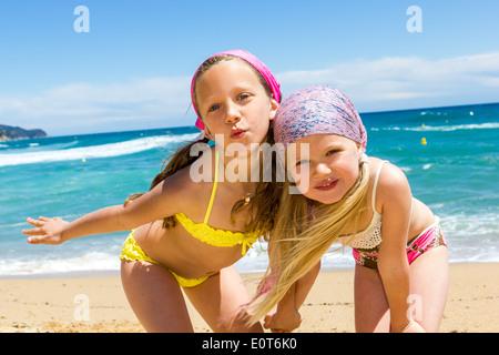 Close up portrait of two girlfriends in swim wear on beach. - Stock Photo