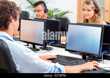 Group of students working on computers in classroom. - Stock Photo