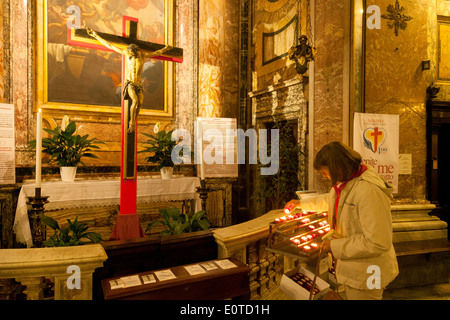 A woman lighting a candle in the Catholic Church of St Mary Magdalene ( Santa Maria Maddelena ), Rome, Italy Europe - Stock Photo