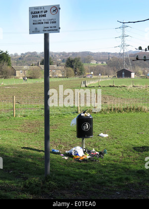 Unemptied litter bin spewing rubbish on to the grass. - Stock Photo