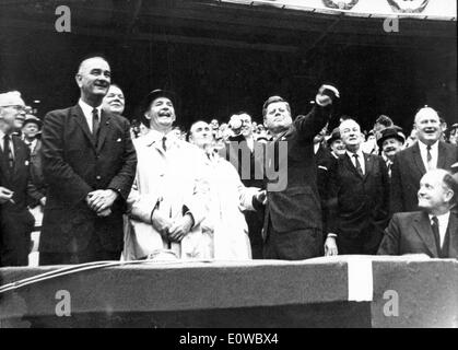 President Kennedy throws the first pitch as President Johnson watches - Stock Photo