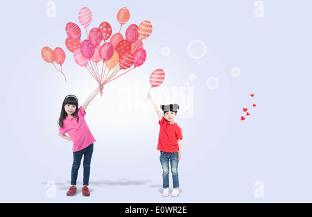 two girls holding balloons - Stock Photo