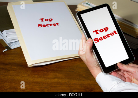 Woman using tablet device to photograph corporate secrets - Stock Photo
