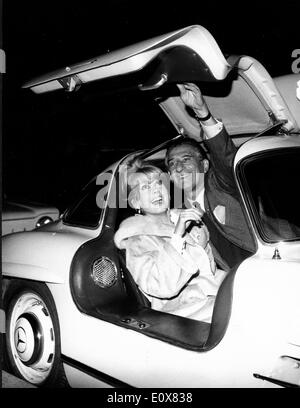 Actress Catherine Deneuve in a sports car with man - Stock Photo