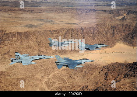 US and Royal Jordanian Air Force F-16 Fighting Falcons and a US Marine Corps F-18 Hornet fighter aircraft fly in - Stock Photo