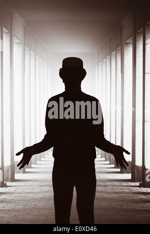Silhouette of man with hat standing in backlit colonnade showing his hands. Conceptual image of magic, mystery and the paranormal.