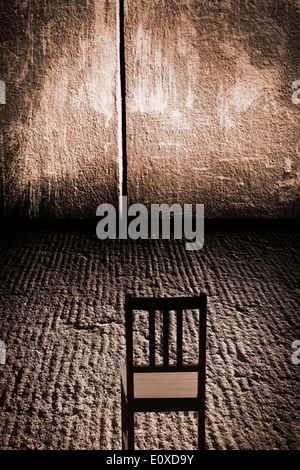 One empty chair in an abandoned   room with concrete wall and rough grungy floor, possibly set up for interrogation. - Stock Photo