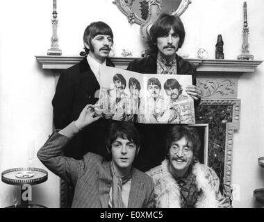 The Beatles holding up a poster of themselves - Stock Photo