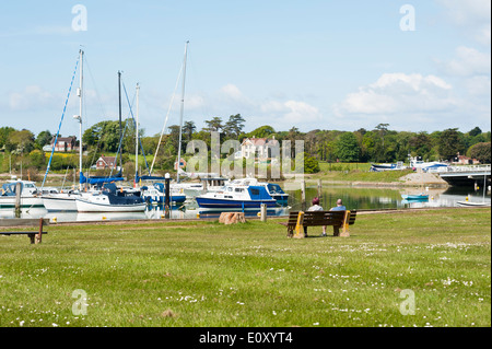 Coastal image showing yarmouth harbour on the isle of wight in the uk with two people relaxing on a wooden bench - Stock Photo
