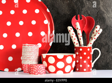 Modern Red and White Polka Dot Kitchen with large platter plate, cupcake pans, bowl, coffee mug, cutlery and serving - Stock Photo