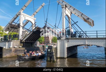 Amsterdam Magere Brug, Skinny Bridge, small boat passing drawbridge. A bridgeman on bicycle is closing the bascule - Stock Photo