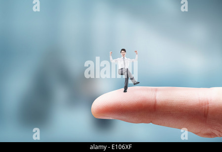 a business man sitting on a finger - Stock Photo