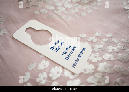 A 'do not disturb' door sign in English French and German on a bed in a hotel room UK - Stock Photo