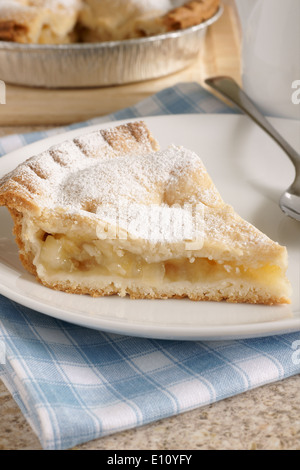 Slice of hot apple pie dusted with icing sugar - Stock Photo
