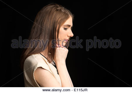 young woman in profile with her hands clasped below her chin as if in prayer - Stock Photo