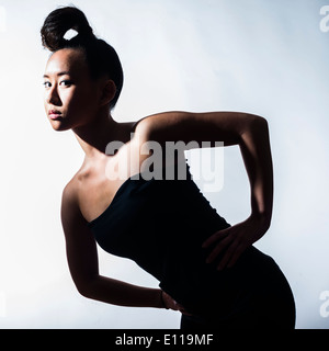 A young slim asian chinese woman girl with her hair tied tightly on her head hands on hips - Stock Photo