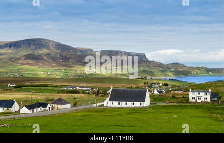 STAFFIN VILLAGE AND RANGE OF HILLS THE TROTTERNISH RIDGE BEHIND THE HOUSES ON THE ISLE OF SKYE SCOTLAND - Stock Photo