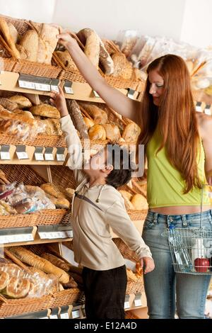 May 15, 2009 - May 15, 2009 - Grocery store shopping - Red hair woman and child choosing bread in a supermarket - Stock Photo