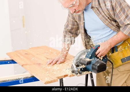 Nov. 24, 2010 - Nov. 24, 2010 - Home improvement - handyman cut wood with jigsaw in workshop - Stock Photo