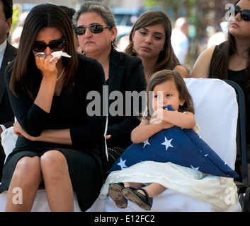 Vicki Baker, left, the widow of U.S. Army Sgt. 1st Class Jeffrey Baker, weeps while their daughter holds a US flag - Stock Photo