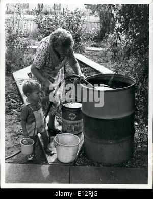Feb. 25, 2012 - Mrs. E.J.Dwyer, watched by grandson Raymond Colvin, fills her 44-galon drum after the arrival of - Stock Photo