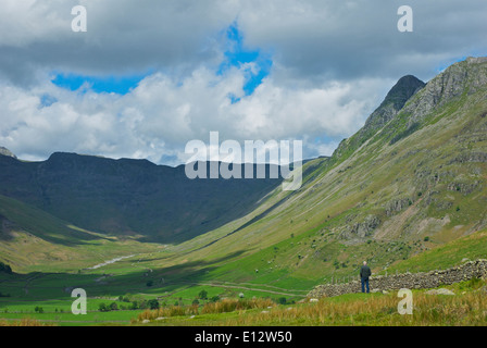 Man looking down over the valley of Mickleden, Great Langdale, Lake District National Park, Cumbria, England UK - Stock Photo