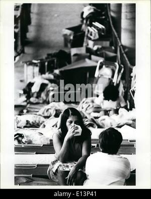 Mar. 22, 2012 - A woman Cuban refugee sits on her cot on a ramp in the Orange Bowl in Miami as she drinks a carton - Stock Photo