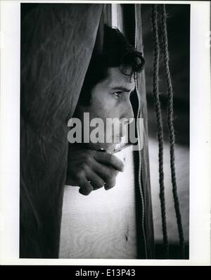 Mar. 22, 2012 - A Cuban refugee peers out of the his in which he is housed as he munches on an apple. The refugee - Stock Photo