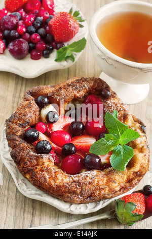 Mini german pancake with mix of berries and tea. Selective focus. - Stock Photo