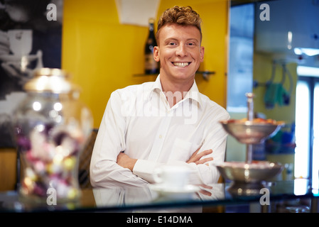People in cafeteria, portrait of happy young man working as barman, smiling at camera behind counter - Stock Photo