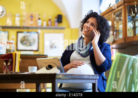 People in cafeteria, with pregnant woman drinking espresso coffee sitting at table with ipad and talking on phone - Stock Photo