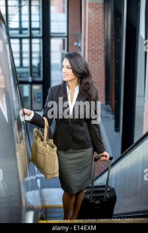 Mixed race businesswoman riding escalator - Stock Photo