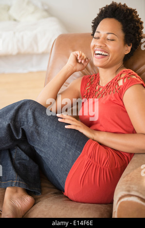 Black woman laughing in armchair - Stock Photo