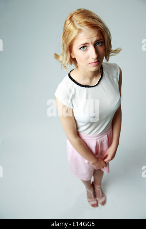 Compassionate young girl standing on gray background - Stock Photo