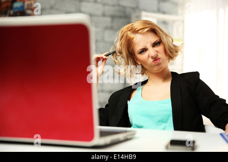 Young funny woman sitting at her workplace in office - Stock Photo