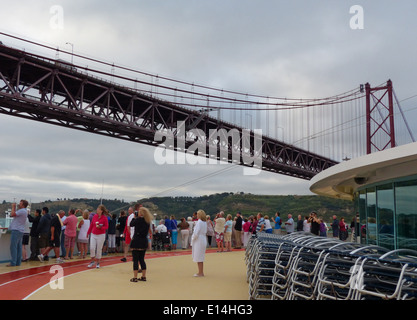 People watching as a cruise ship passes under a low bridge in Lisbon, Portugal - Stock Photo
