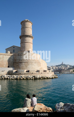 Two Girls in Front of the Lighthouse of Fort Saint Jean at the Entrance to the Vieux Port or Vieux Port Marseille - Stock Photo