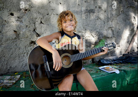 Girl, 11, holding a guitar, having guitar lessons as part of the Sao Martinho social project for street children, - Stock Photo