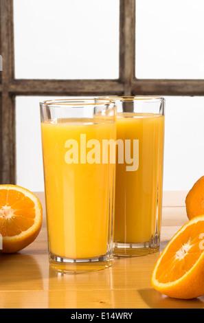Orange juice - Two glasses of orange juice on table with oranges - Stock Photo