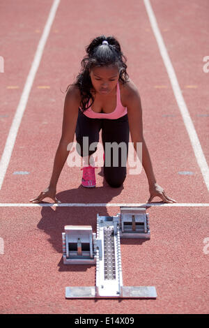 Sporty young woman getting ready on running track, starting block - Stock Photo