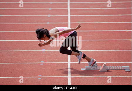 Sporty young woman starting from starting block to run on running track - Stock Photo