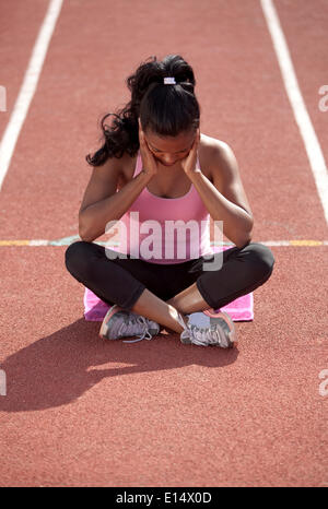 Sporty young woman, meditating, sitting on race track, getting mentally ready - Stock Photo