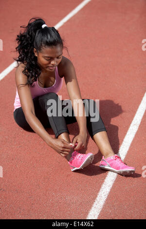Sporty young woman, sitting on race track, tightening her running shoes - Stock Photo