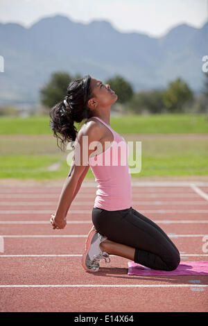 Sporty young woman on running track, stretching arms - Stock Photo